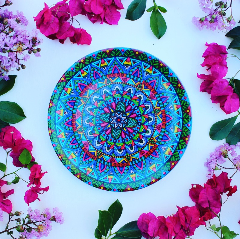 Beautiful and colourful mandala plates surrounded by pink and purple flowers
