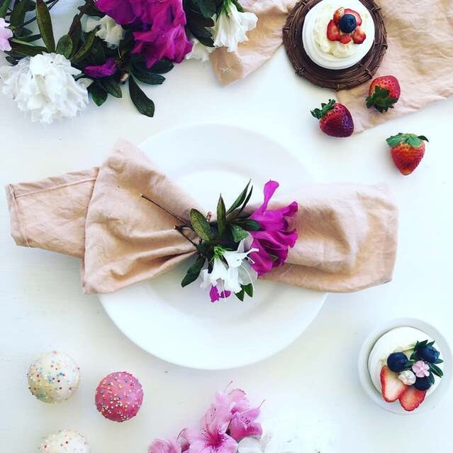 Unique napkin rings placed around pink botanically dyed linen napkins
