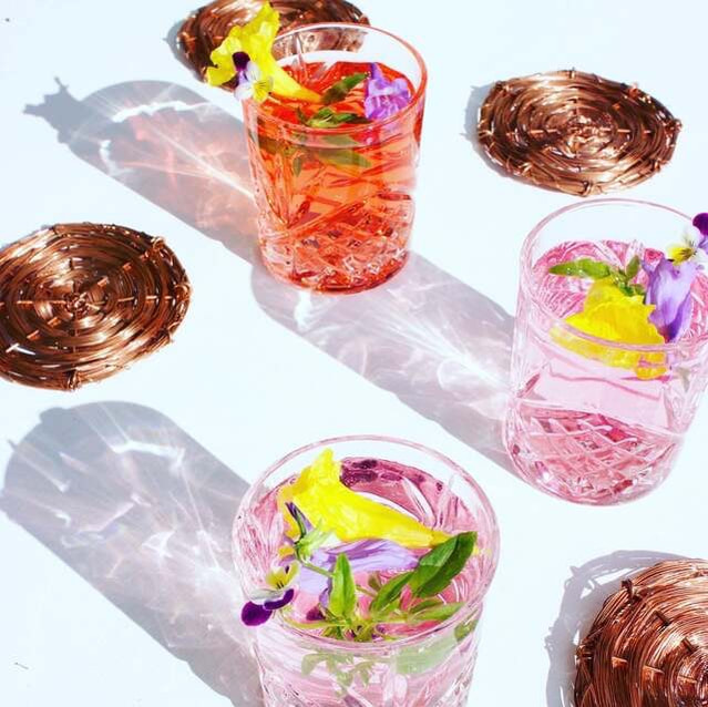 Beautiful cocktails with edible garnishes served on bespoke coasters