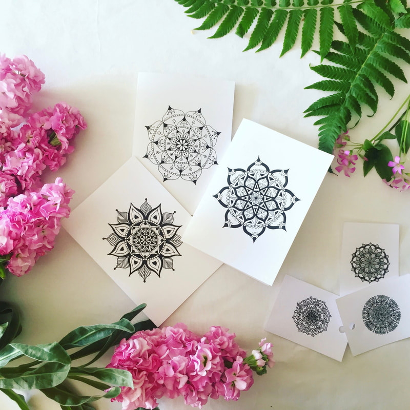 Black and white gift cards styled with pink flowers and greenery