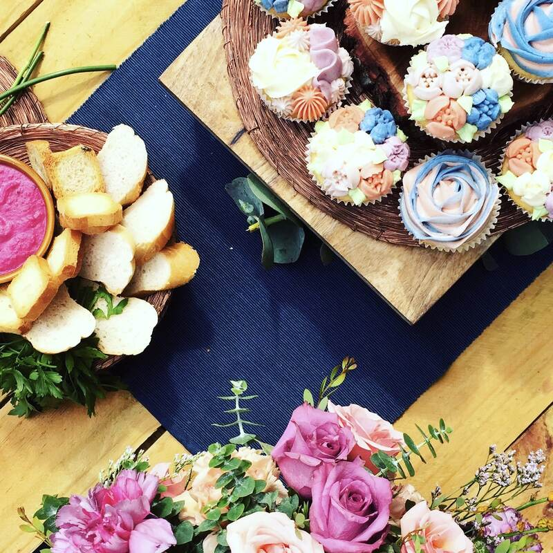 Beautiful tableware surrounded by colourful cupcakes and pretty flowers