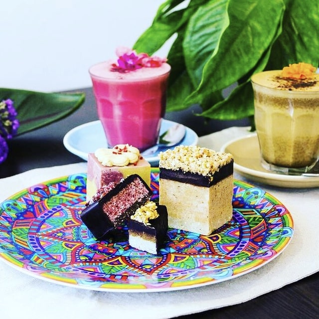 Mandala plate loaded with raw, vegan treats with turmeric and beetroot lattes on the side